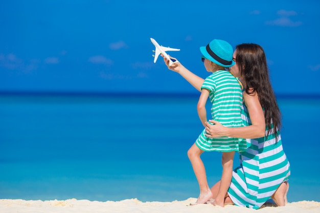 Young woman and little girl with miniature of airplane at beach Premium Photo