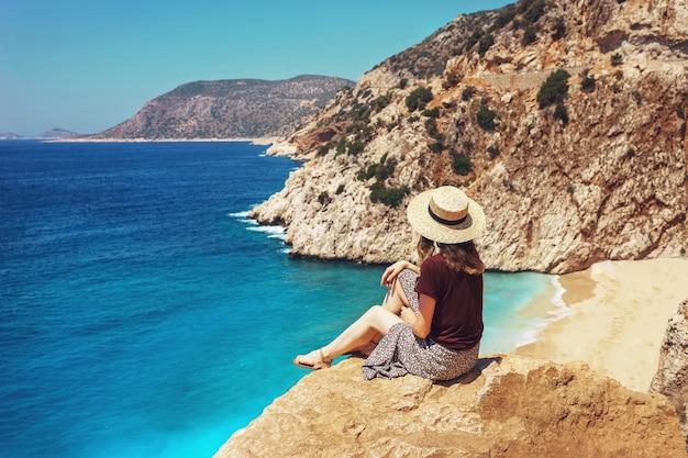 젊은 여자가 아름다운 Kaputas 해변을 바라보고, 휴가 기간 동안 밝은 여름날에 리시아 해안을 여행하십시오. 프리미엄 사진