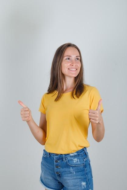 Giovane donna che guarda lontano con i pollici in su in maglietta gialla, pantaloncini e guardando allegra Foto Gratuite