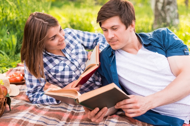 Young woman looking at boyfriend reading book Free Photo