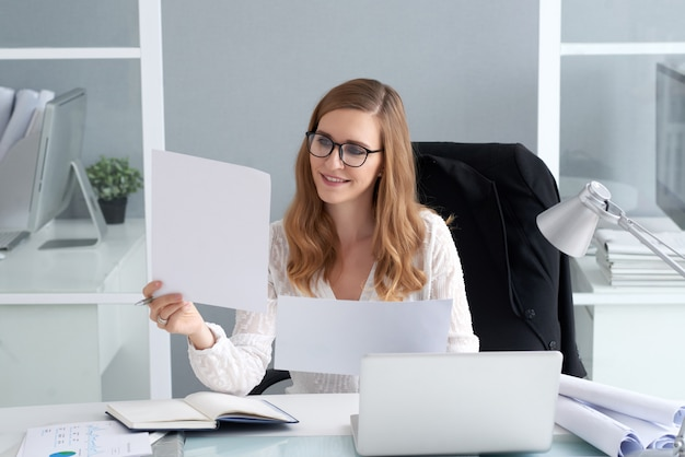 Young woman looking at documents Free Photo