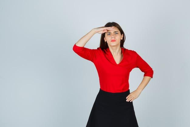 빨간 블라우스에 엉덩이에 손을 잡고 머리 위로 손으로 멀리 찾고 젊은 여자 무료 사진