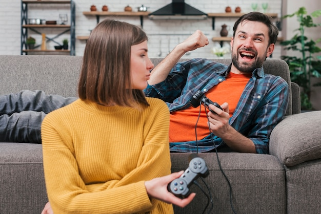 Young woman looking at her boyfriend lying on sofa cheering after winning the video game Free Photo