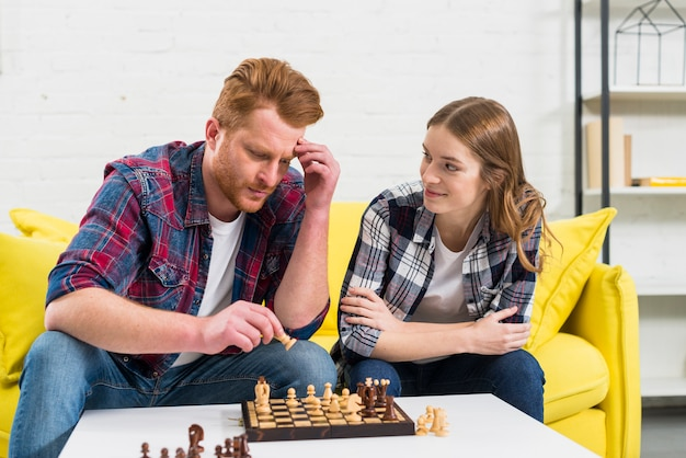 Young woman looking at her thoughtful boyfriend playing the chess Free Photo
