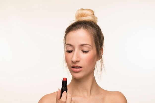 Young woman looking at lipstick Free Photo