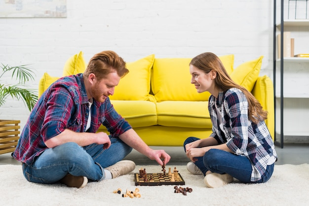 Young woman looking at man playing the chess game in the living room Free Photo