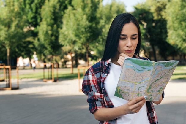 Young woman looking at map and thinking at park Free Photo
