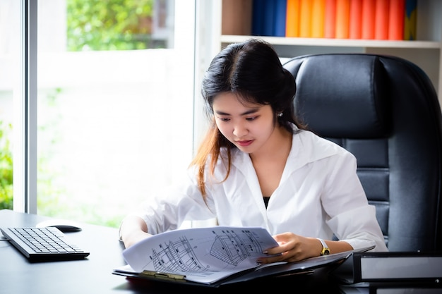 Young woman looking paper work in folder Free Photo