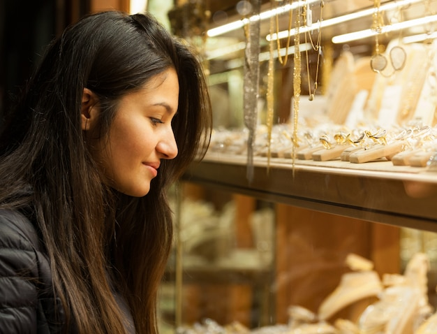 Young woman looking at the showcase of an outdoor jewelry Premium Photo