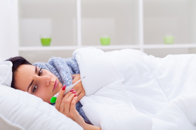 Young woman looking at thermometer while holding it in hands and lying in bed Premium Photo