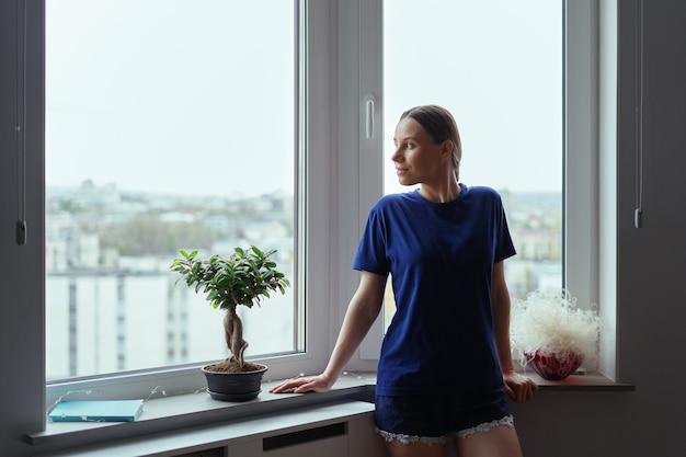 街の窓から見ている若い女性 無料写真