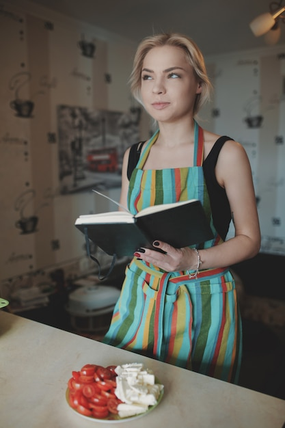 Young woman looking up in a recipes book Free Photo