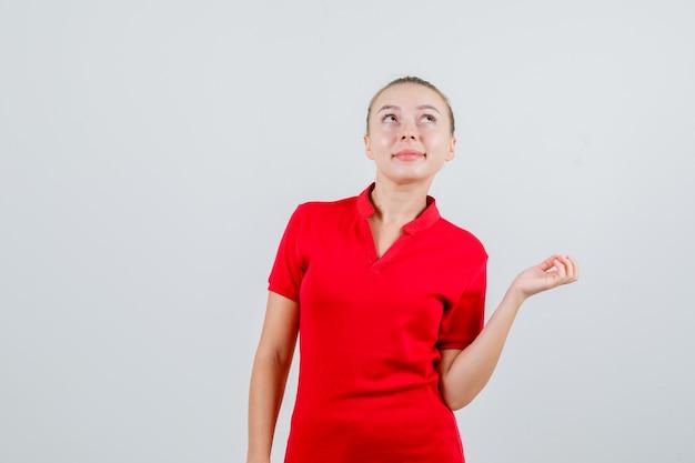 Молодая женщина смотрит вверх в красной футболке и выглядит обнадеживающей Бесплатные Фотографии