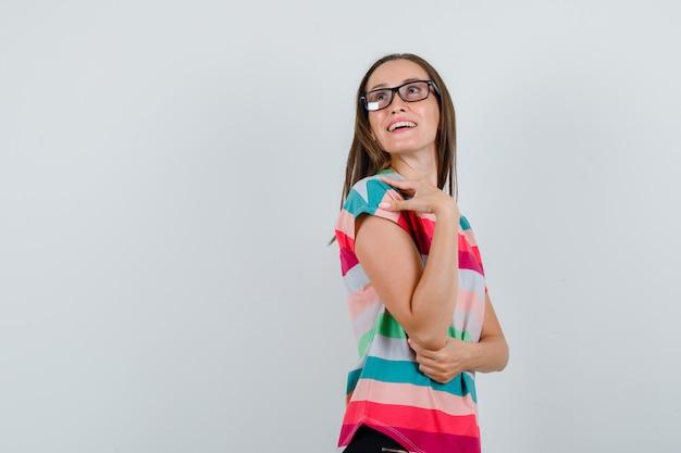 Молодая женщина смотрит вверх в футболке, штанах, очках и смотрит с надеждой, вид спереди. Бесплатные Фотографии