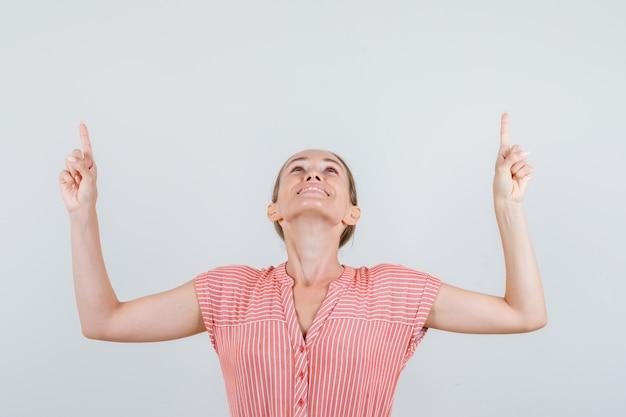 Молодая женщина смотрит вверх с пальцем в полосатом платье и выглядит веселой, вид спереди. Бесплатные Фотографии