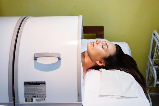 Giovane donna sdraiata sul tavolo del cosmetologo durante la procedura di ringiovanimento Foto Gratuite