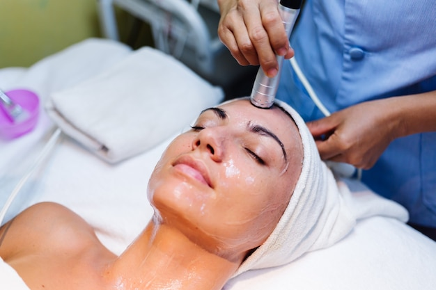 Young woman lying on cosmetologist's table during rejuvenation procedure Free Photo