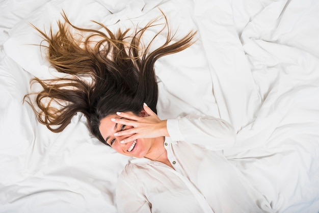 Young woman lying on crumpled bed peeking through finger Free Photo