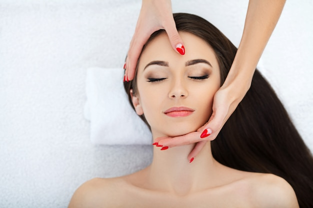 Young woman lying on a massage table,relaxing with eyes closed. woman. spa salon Premium Photo