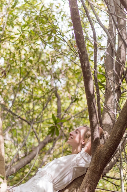 Young woman lying on a tree and resting Free Photo