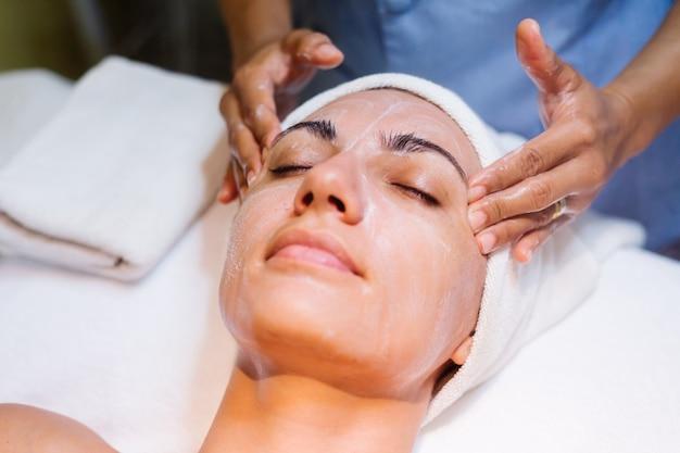 Молодая женщина, лежа на столе косметолога во время процедуры омоложения Бесплатные Фотографии