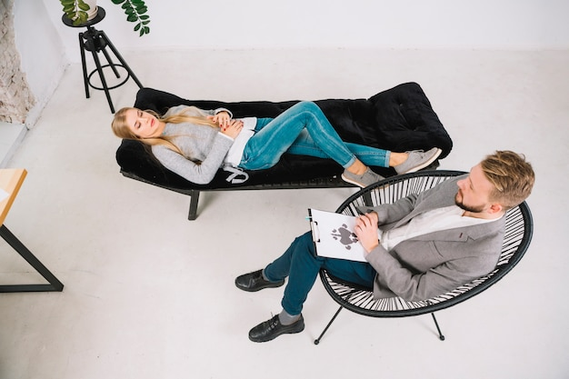 心理学者の診断ロールシャッハ・インクブロットテストで治療を受けてソファに横になっている若い女性 Premium写真