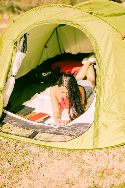 Young woman lying in tent with smartphone Free Photo