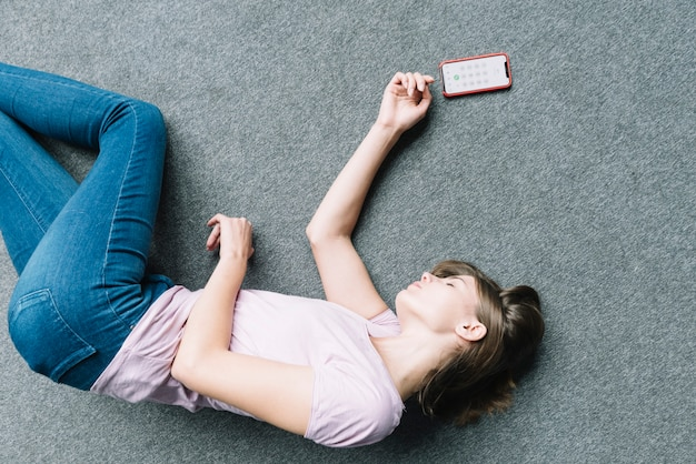 Young woman lying unconsciously on carpet near smart phone Free Photo
