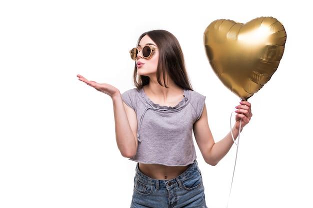 Молодая женщина делает воздушный поцелуй воздушным шаром в форме сердца Бесплатные Фотографии