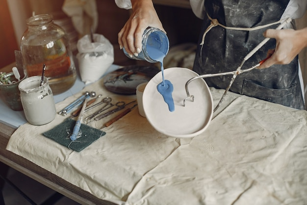 Young woman makes pottery in workshop Free Photo