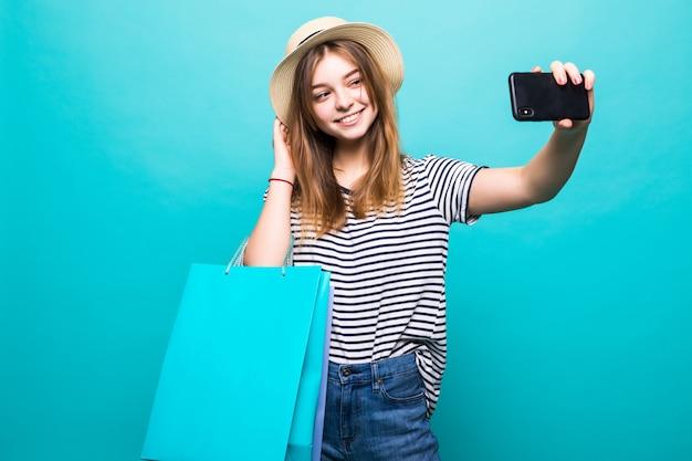 쇼핑을 위해 컬러 가방과 함께 앉아 스마트 폰에 셀카를 만드는 젊은 여자 무료 사진