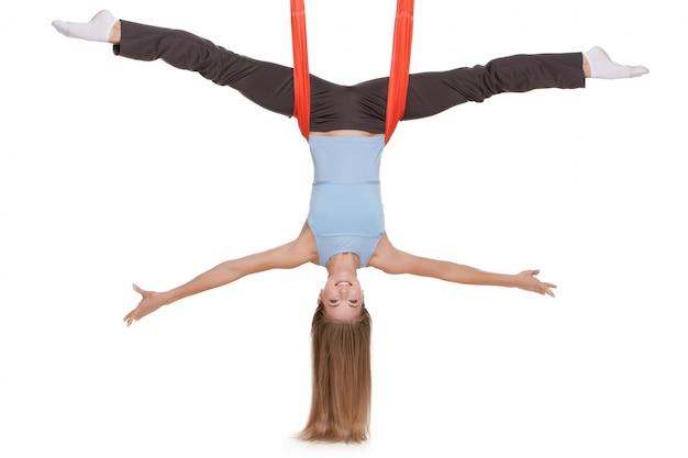 Молодая женщина делает антигравитационные упражнения йоги в растяжке шпагата Бесплатные Фотографии