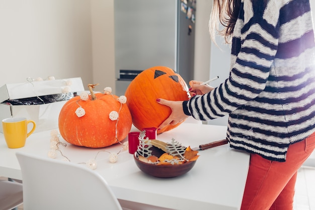 Young woman making jack-o-lantern for halloween on kitchen. drawing eyes, nose and mouth with pen on pumpkin Premium Photo