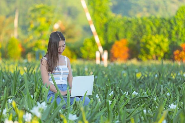Молодая женщина делает заметки в блокноте, сидя в цветнике Бесплатные Фотографии