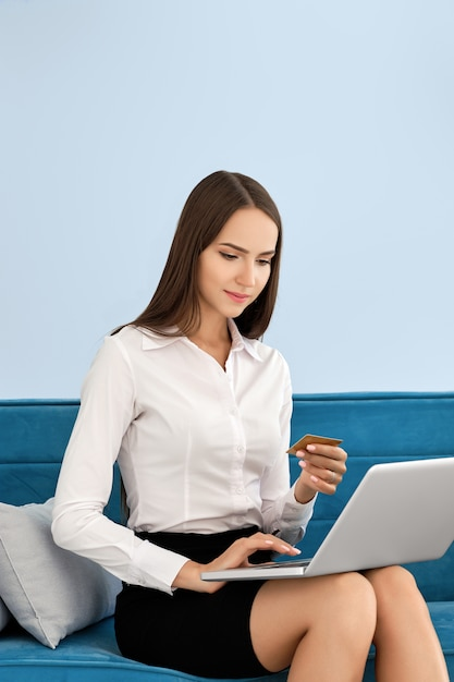 Young woman making online payment sitting on sofa Premium Photo