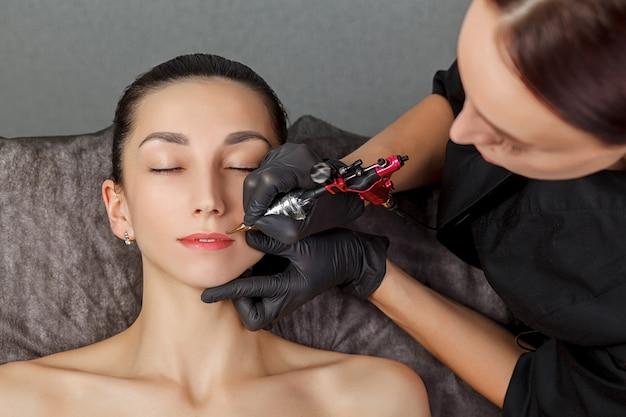 Молодая женщина делает перманентный макияж в косметологическом салоне Premium Фотографии