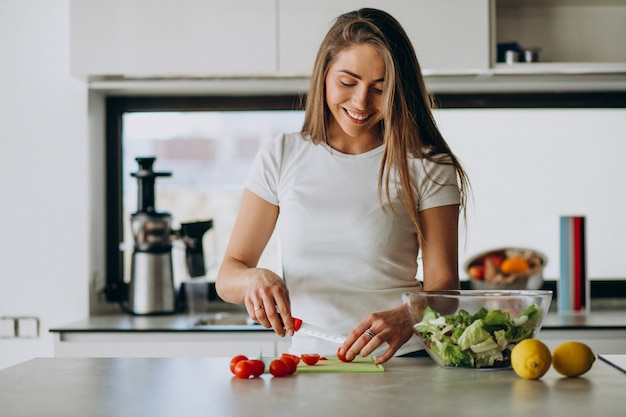 Young woman making salad at the kitchen Free Photo