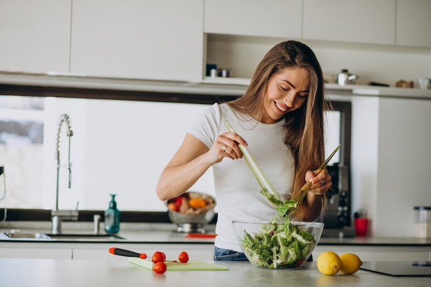 Young woman making salad at the kitchen Free Photo