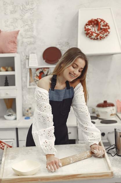 Giovane donna che produce biscotti a forma di per natale. soggiorno decorato con decorazioni natalizie sullo sfondo. donna in grembiule. Foto Gratuite