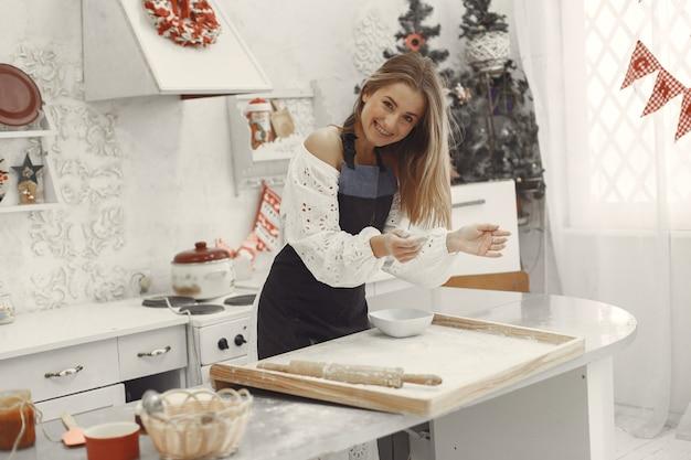 Giovane donna che produce biscotti a forma di per natale. Foto Gratuite