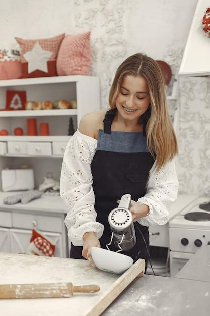 크리스마스 모양의 쿠키를 만드는 젊은 여자. 백그라운드에서 크리스마스 장식으로 장식 된 거실. 앞치마에 여자. 무료 사진