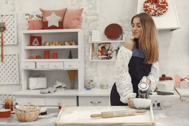 クリスマスのために形をしたクッキーを作る若い女性。バックグラウンドでクリスマスの装飾で飾られたリビングルーム。エプロンの女性。 無料写真