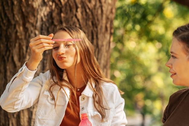Giovane donna che fa le bolle di sapone accanto alla sua amica Foto Gratuite