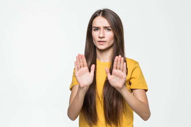 Young woman making stop gesture with her hand isolated on a white wall Free Photo