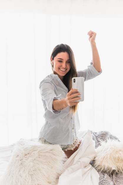 Young woman making video call on smartphone dancing Free Photo
