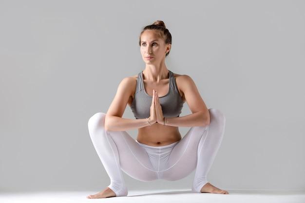 Young woman in malasana pose, grey studio background Free Photo