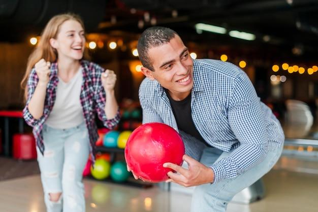 Giovane donna e uomo in piedi in un club di bowling Foto Gratuite