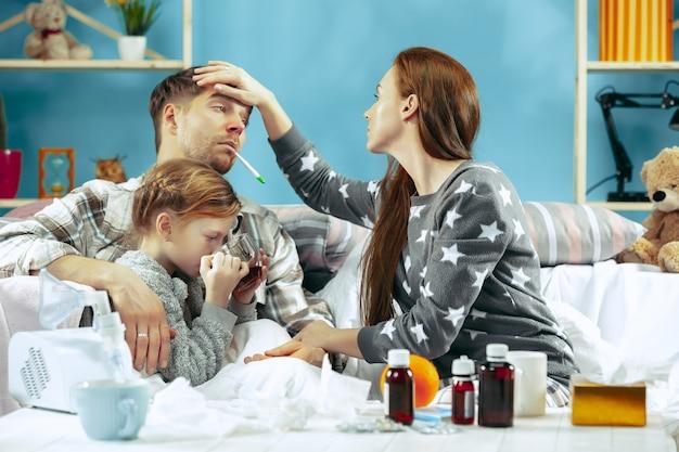 La giovane donna e l'uomo con la figlia ammalata a casa. trattamento domiciliare. combattere con una malattia. assistenza medica. insufficienza familiare. l'inverno, l'influenza, la salute, il dolore, la paternità, il concetto di relazione Foto Gratuite