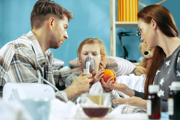 La giovane donna e l'uomo con la figlia ammalata a casa. trattamento domiciliare. combattere con una malattia. assistenza medica Foto Gratuite