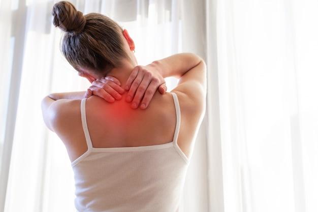 Молодая женщина массирует шею из-за боли в шее, растяжения мышц. Premium Фотографии